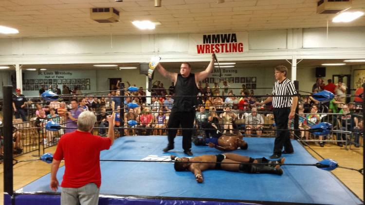 Kevin Lee Davidson hoists his newly-won MMWA Heavyweight Championship and Survivor Championship belts over the defeated A.J. Williams and Da'Marius Jones, Sept. 12.  Photo: Timothy Miller